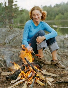 Young woman sitting at camp fire, holding fried sausage